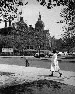 Public health student Sheila Joardar walking along Monument street with Johns Hopkins Hospital in background