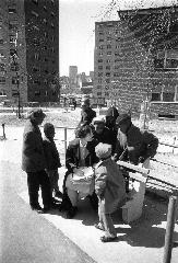 Children gathered around student public health nurse Carolyn Griggs on park bench